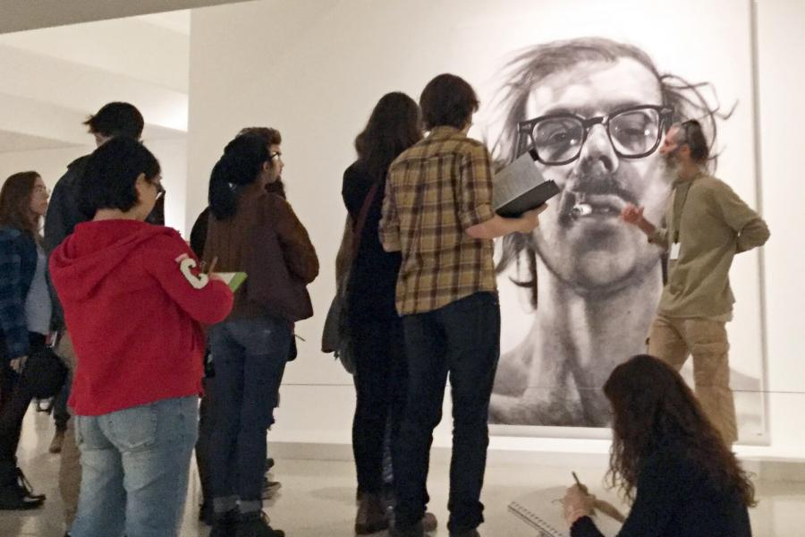 A man stands in front of a piece of artwork, students gather around and listen to him speak about the piece.
