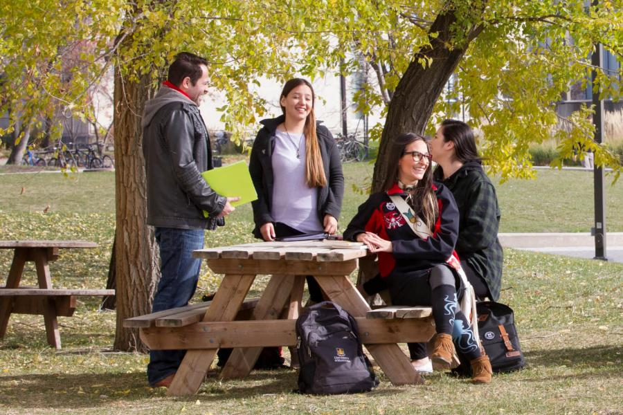 Four Indigenous students sit and stand together talking outdoors at a picnic table.