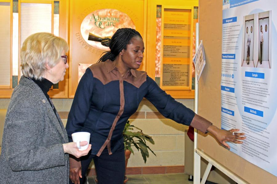 A nursing student explains her work during a poster competition.