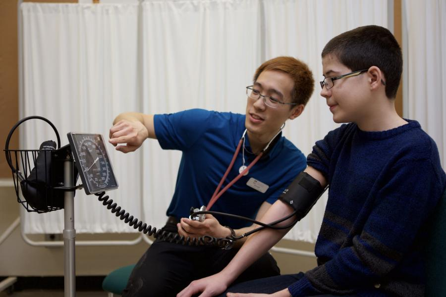 A rehabilitation sciences student uses a blood pressure monitor on a young patient and points to the monitor to show how it works.