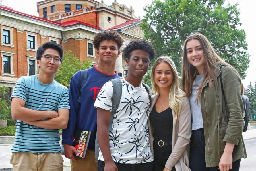 A group of five undergraduate students stand together in front of the University of Manitoba Administration building.