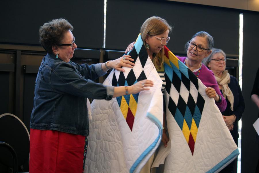 Two women place an awarded blanket over the back of another.