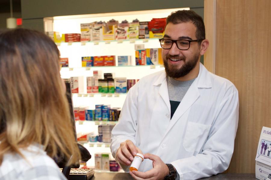 Pharmacy student serves a customer in a retail setting