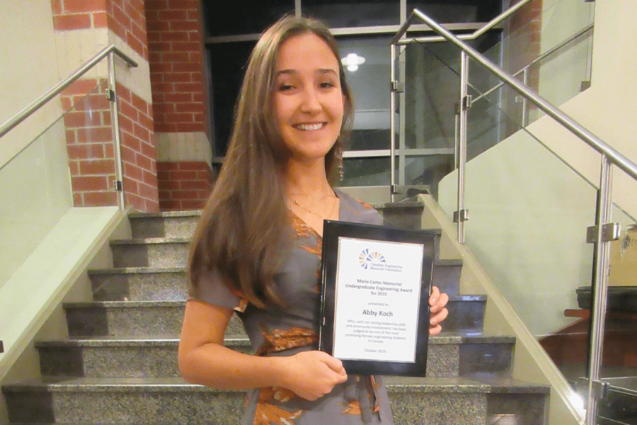 A biosystems engineering student holds an award she has received.
