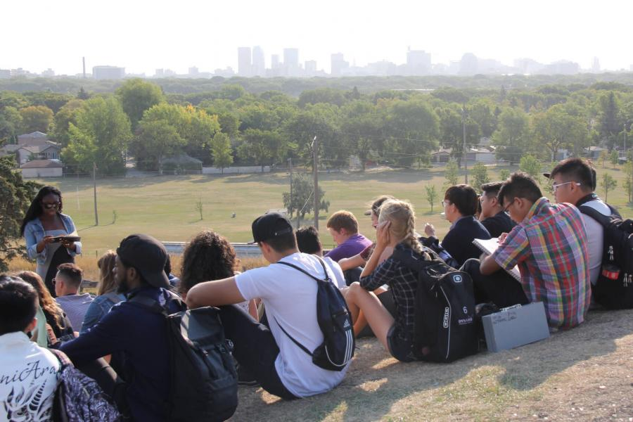 Students seated on the ground at the top of a hill overlooking a scenic city landscape.