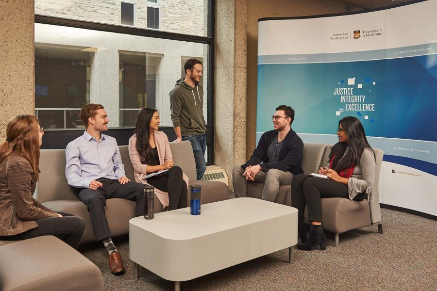 Six students sit together talking in a lounge area.
