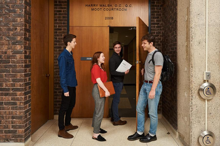 Four students walk into a building together.