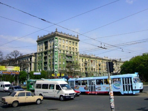 Image of car and buses passing a large cream building