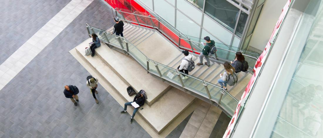An elevated view of a busy staircase in the interior of the Engineering and Information Technology Complex.