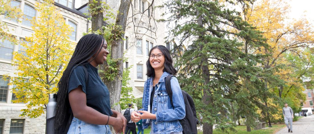 Two students stand together talking outside of the Tier building at the University of Manitoba Fort Garry campus.
