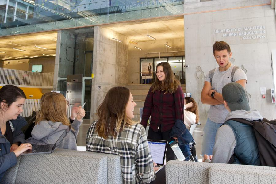 A group of seven students hanging out and studying together inside the Active Living Centre.