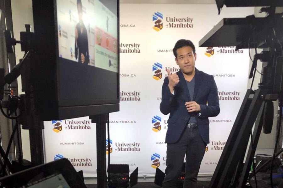Toby Le giving his 3MT presentation in front of a video camera at the University of Manitoba.