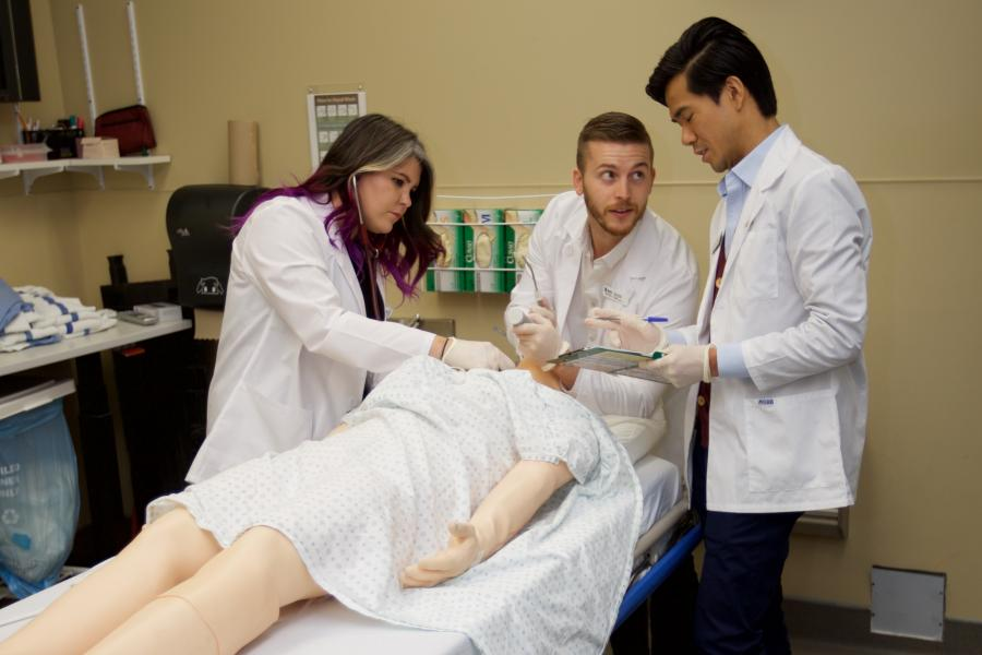A group of residents work on a medical manikin