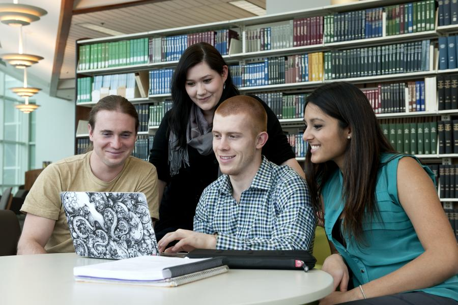 Group of four students look at a laptop screen, smiling.