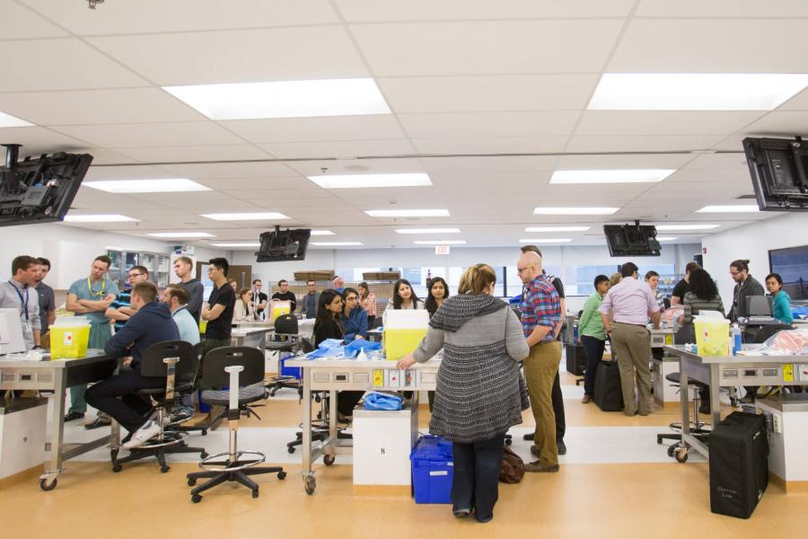 Medicine students work in a large room in groups at separate tables.