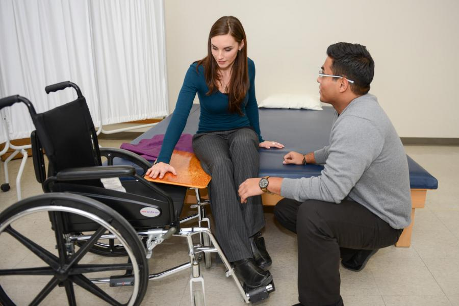 A Rehabilitation Sciences student assists a client into a wheelchair from a bed.