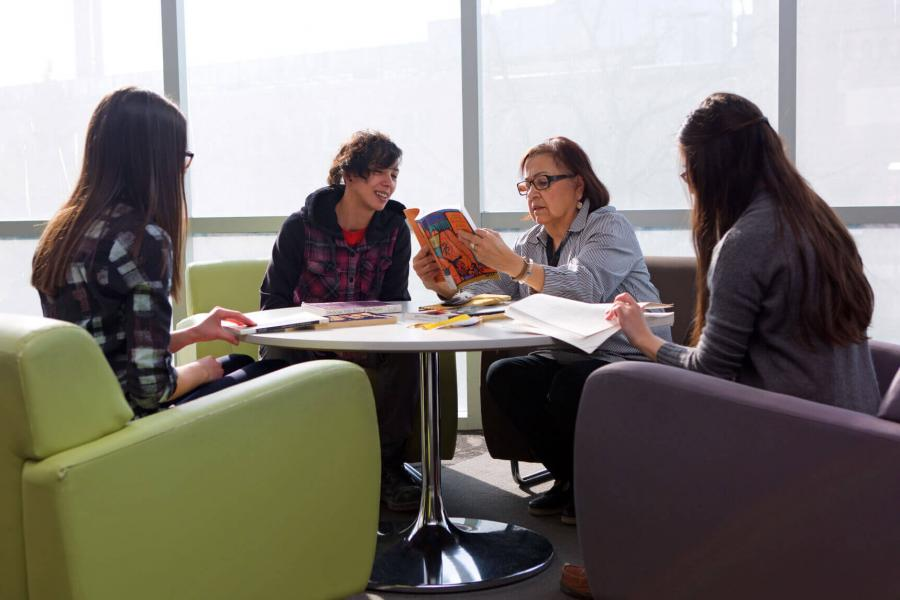 Four people sit around a circular table and look at books together.