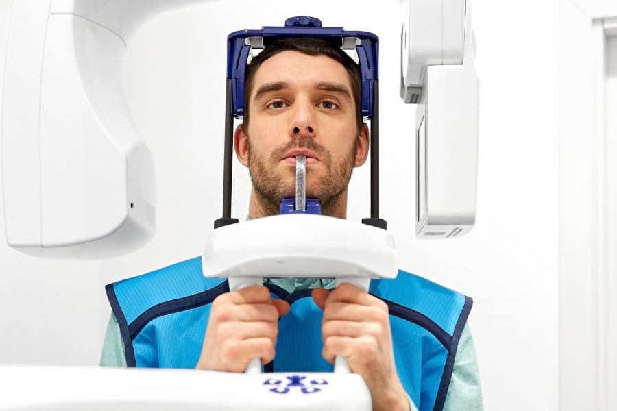 Patient in a blue protective vest has his teeth scanned in a large imaging machine.