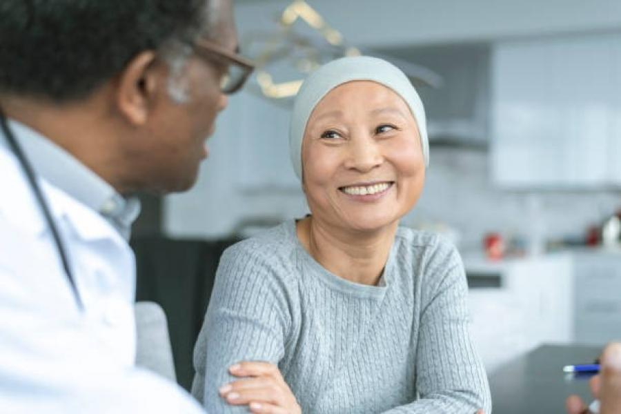 Smiling patient wearing a head scarf talks to her physician.