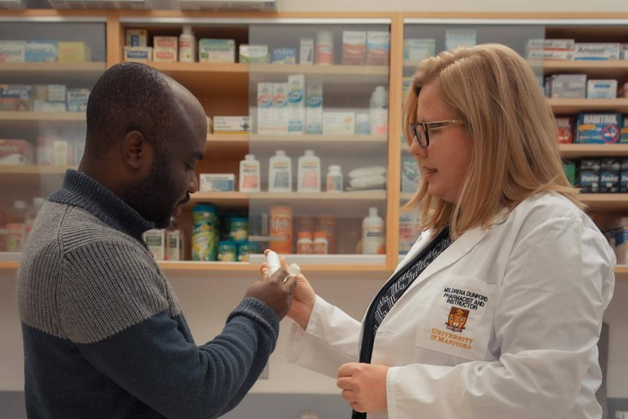 A pharmacist discusses a prescription with a customer
