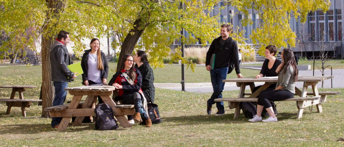 Seven Indigenous students sit and stand together outdoors at two picnic tables at the Fort Garry campus.