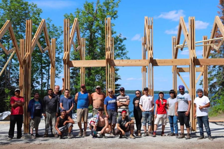 Members of the Engineering and Architecture faculties stand together in front of a ceremonial structure they have built at Shoal Lake 40.