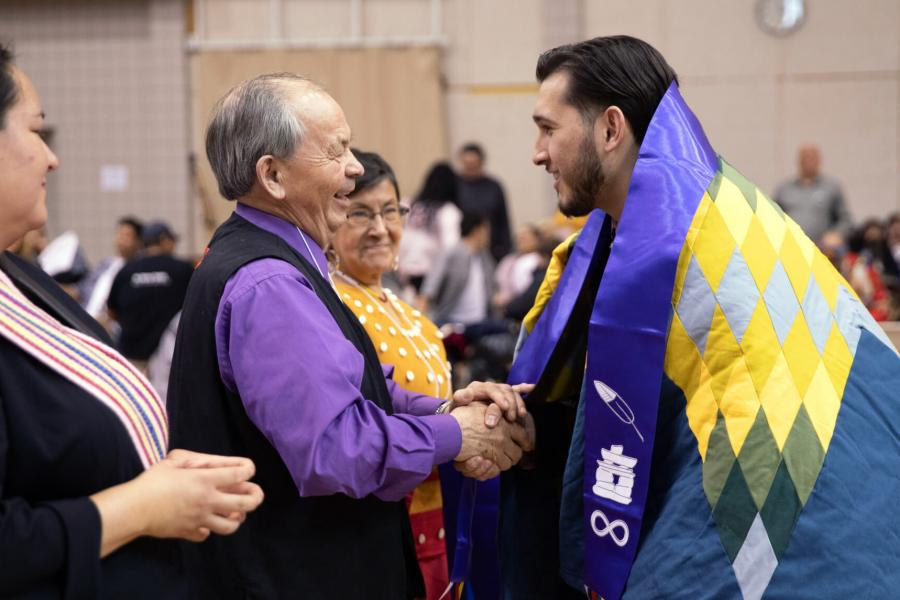 A student receives his Indigenous scarf at the graduation PowWow.