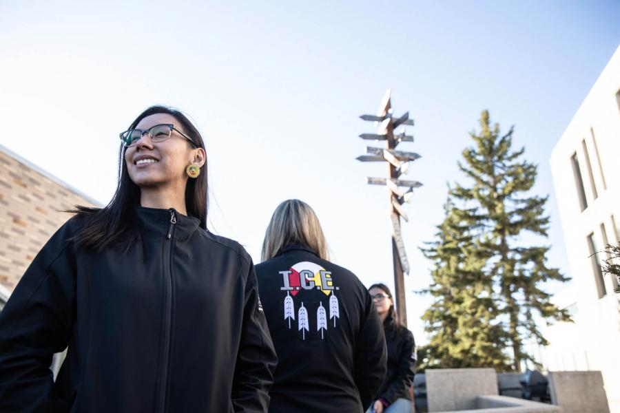 Three Indigenous students stand together, each of them wearing Indigenous Circle of Empowerment jackets.