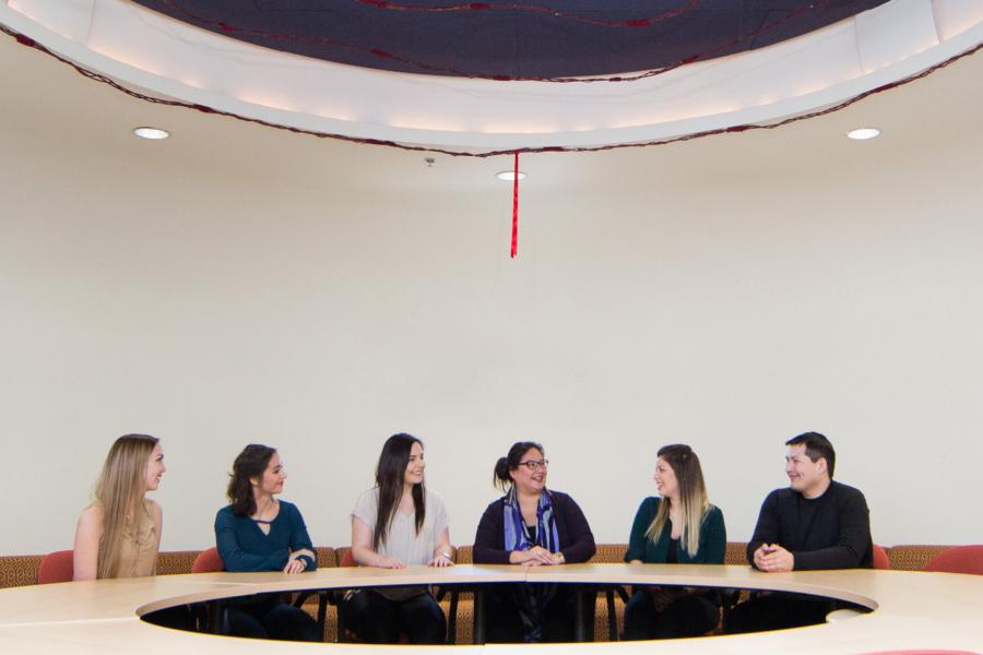 Indigenous student advisor Carla Loewen sits at a circular table with several students at Migizii Agamik.