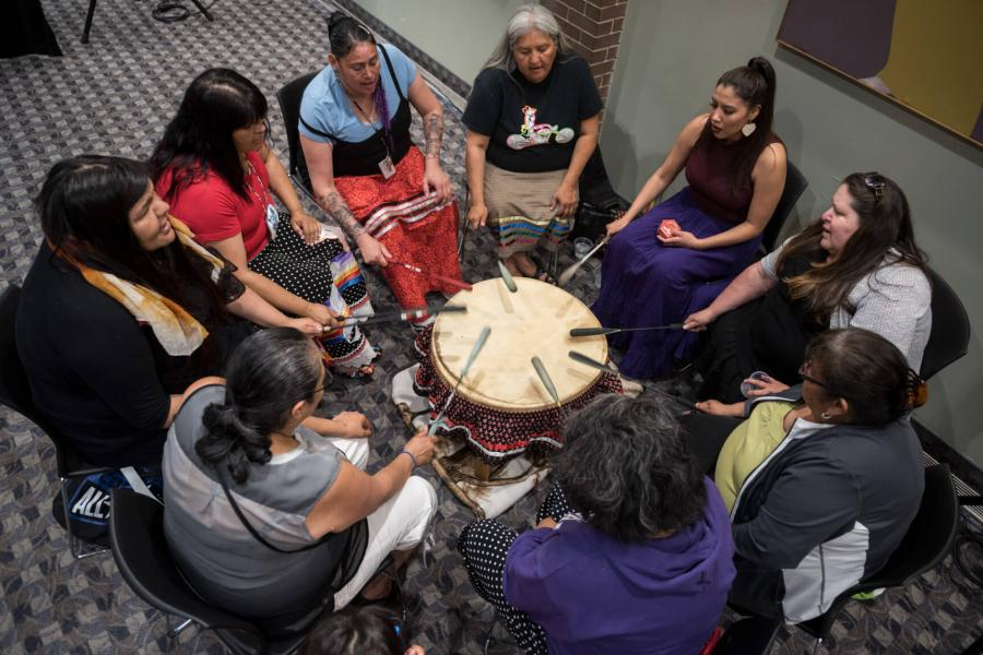 A group of women gathered in a circle beating a PowWow drum.