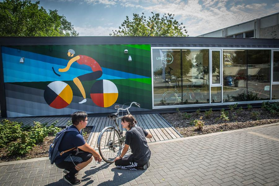 The UMCycle Bike kiosk and Cycle Plaza features a mural from artists Dee Barsy and Kenneth Lavalee.