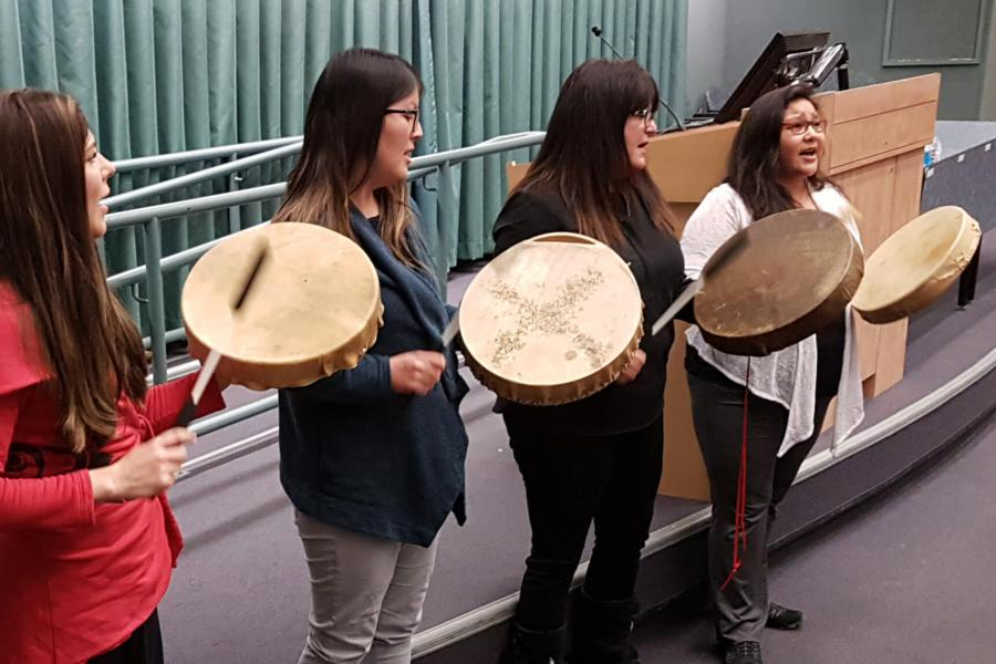 Four women stand in a row together singing and beating drums.