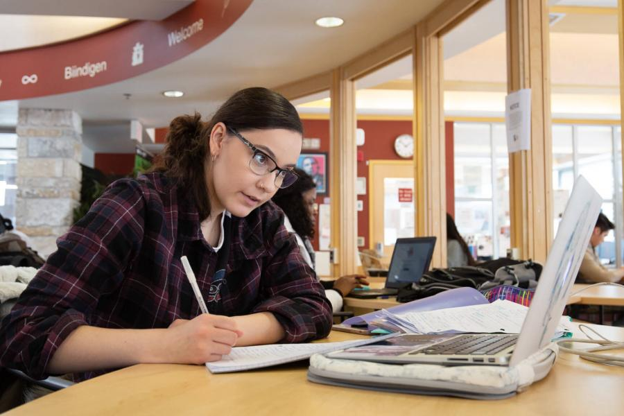 An Indigenous student studies at a table inside Migizii Agamik - Bald Eagle Lodge.