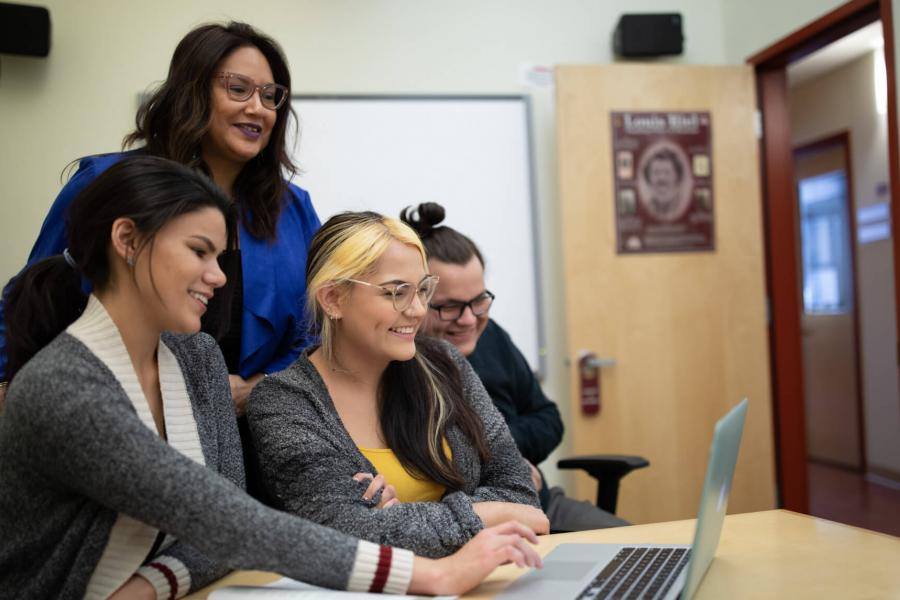 Three smiling students gather around a laptop with Indigenous Student Advisor Carla Loewen.