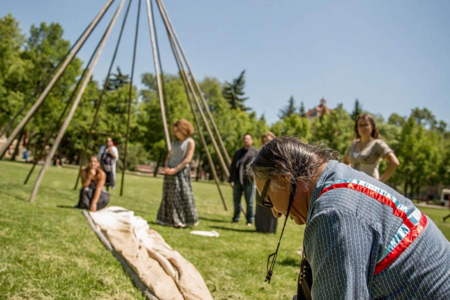 Carl Stone and several others work on constructing a teepee at the Fort Garry campus.