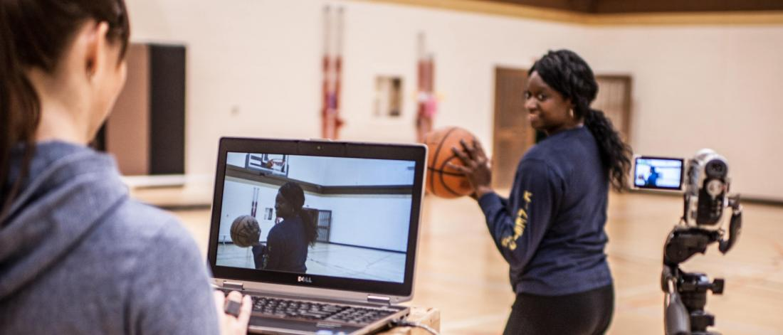 Two researchers in a gymnasium, one stands in front of a laptop and a camera on a tripod while the other prepares to throw a basketball.