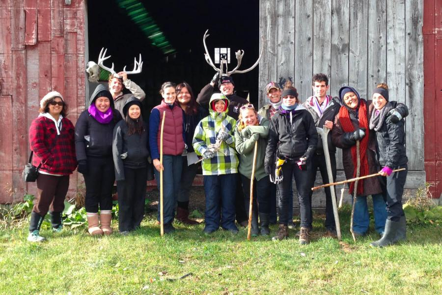 A group of people gather together outside of a barn to pose for a group photo.