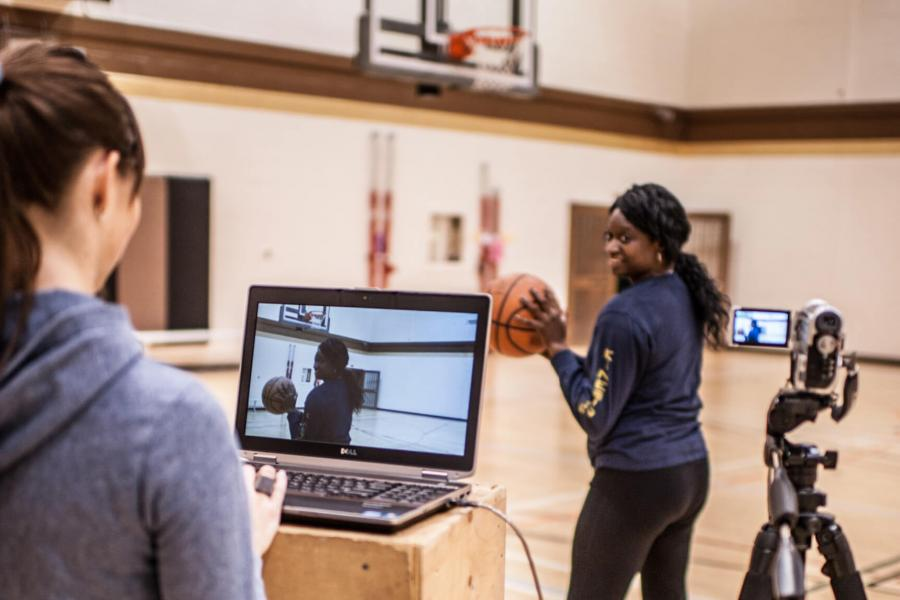 Two students in a gymnasium, one holds a basketball and prepares to throw the ball while the other monitors a laptop and camera.