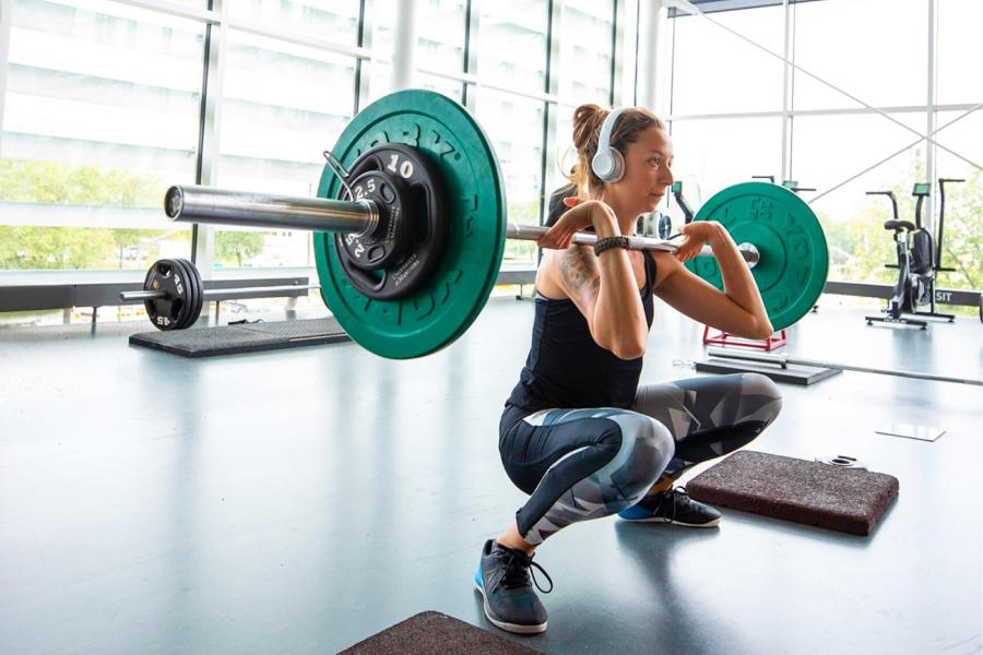 A woman prepares to lift a weighted barbell at the Active Living Centre.
