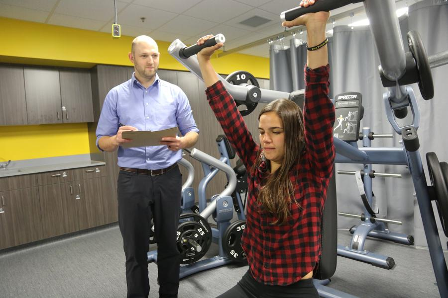 researcher and student conduct research using weight machine