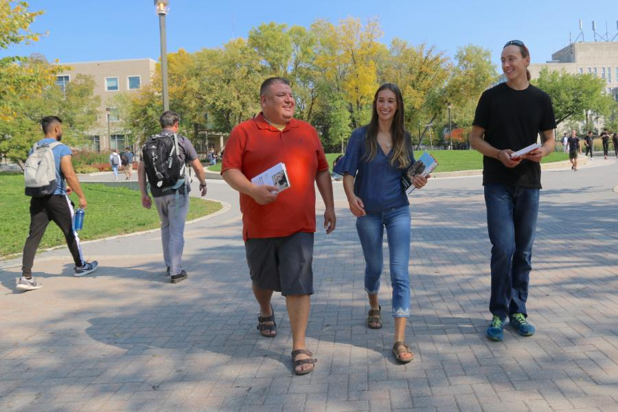 Three people walking together along Curry Place at the University of Manitoba Fort Garry campus.