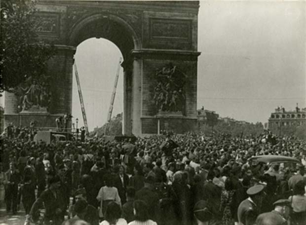 Parisians gather to welcome their liberators. Flags of the U.S.A., Great Britain and Free France are hoisted to fly under the Arc de Triomphe