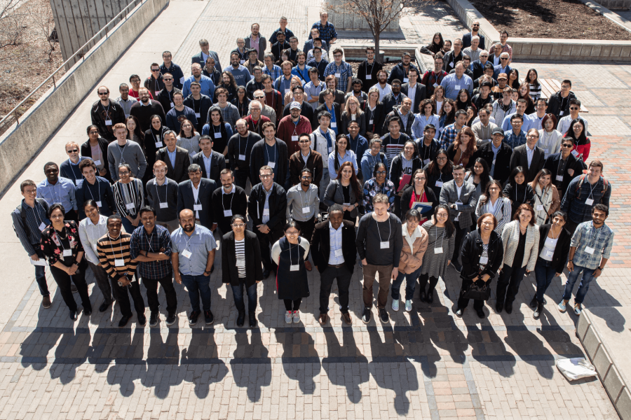 A large group of attendees from the 2019 Manitoba Materials Conference gather together outdoors for a group photo.