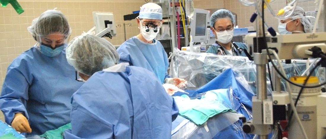 four surgeons in an operating room with a patient on the operating table.