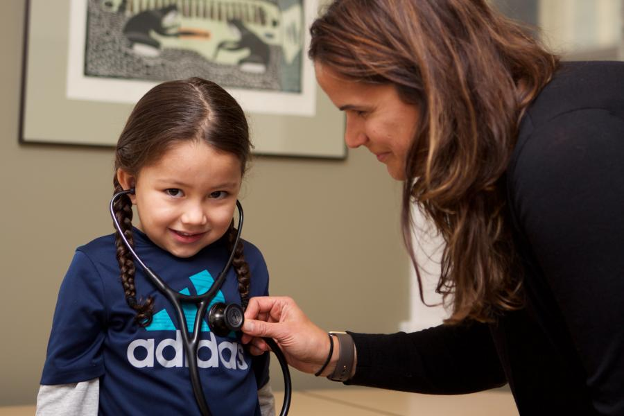 A doctor checking a child patient's hear rate with a stethoscope.