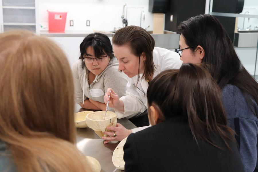 A researcher in a lab coat demonstrating an experiment to a group of high school students.