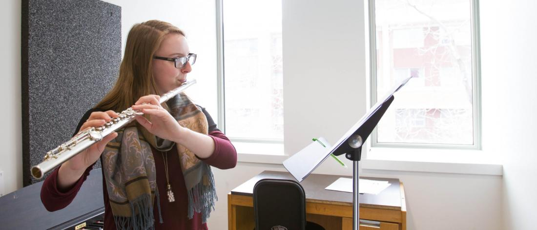 A music student practices the flute in a practice room.