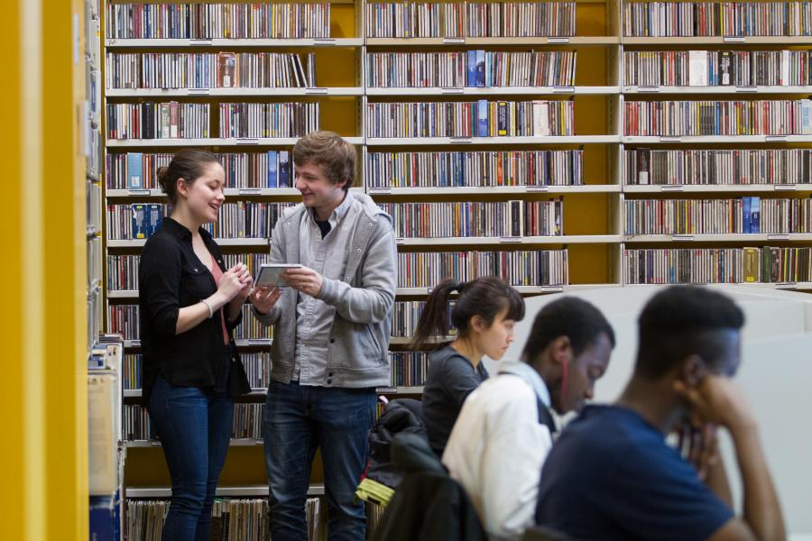 Students stand and talk in front of a large shelf of music while other students are seated and studying inside the music library.