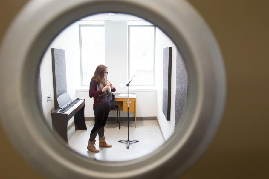 A Desautels Faculty of Music student viewed through a porthole window practicing in a practice room.