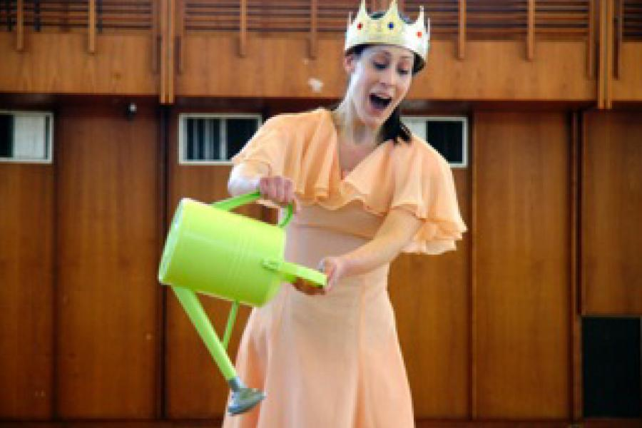A young woman wearing a crown and carrying a watering can sings opera.